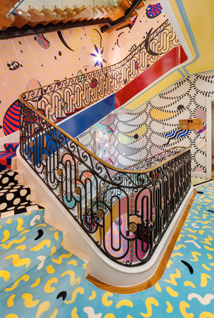 Sasha Bikoff's kaleidoscopic staircase was the buzz of the 2018 Kips Bay Decorator Show House. She set out to create an art installation and technicolor dream, inspired by whimsical 1980s Memphis design. Bikoff designed the rug by rearranging polka dots, squiggly and exaggerated graphics in a modern patchwork, and covered the walls in equally ebullient paper from Voutsa.