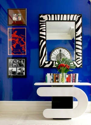 A striking black-and-white lacquered Pierre Cardin console from the '60s commands the space, complemented with a '70s zebra print mirror. In the reflection, a clock reminiscent of antiques like the one in Musee D'Orsay; it's new. The Beatles print is something she found antiquing.