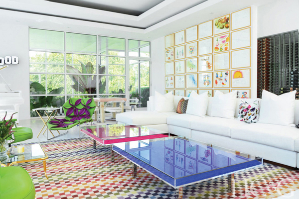 """A pair of Yves Klein plexiglass tables in blue and rose are framed by a multicolored check Missoni rug in the living room of this Bridgehampton, New York, home. A collection of 30 sketches of fruit from the Brimfield antiques markets hang above a white Ralph Lauren sectional. The flower-covered chaise is by Patricia Urquiola for Moroso. Bikoff's mother was a pianist, and the white Steinway grand is a John Lennon special edition, which inside bears the inscription in gold: """"You may say I'm a dreamer,"""" a lyric from the songwriter's """"Imagine."""" Bikoff describes her decorating here as """"a combination of Gauguin's Tahitian Post-Impressionist paintings, pop art, and Brazil."""""""