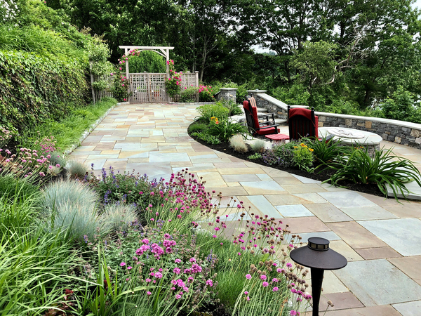 "Curving lines gracefully guide your eye into this garden scene, which Wickie Rowland, the garden's designer, calls ""View With a Room."" The fire-pit area has a view of the water beyond. The garden gate in the background is the entrance to the owners' vegetable garden; the gate's design was inspired by the home's architecture."