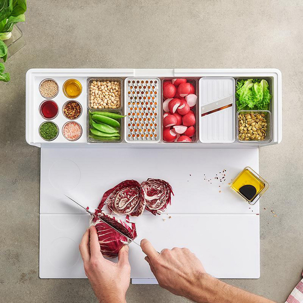 """The French have a phrase for it: mise en place (literally, """"everything in place""""). This modular workstation for meal prep includes bins for ingredients, small containers for spices, fold-out magnetic cutting board (it wraps around the box and the exterior can be customized). In all, 45 features and accessories, storage and trash compartments to cure chaotic counters."""
