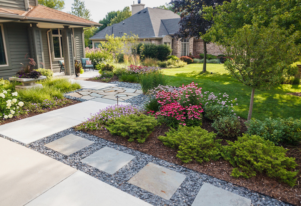 "The materials in this Wisconsin garden's front walk are all inspired by the home's Prairie-style architecture and by materials and colors in the home. James Drzewiecki, the garden's designer, used the lines of the house to guide decisions about the layout of the front walk and flower beds. He calls the design a ""modern prairie."""