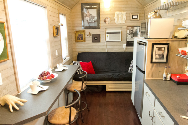 If homeowners are investing in tiny houses, they want to utilize every square inch of space within. This tiny home kitchen features both a bar and comfortable seating area.