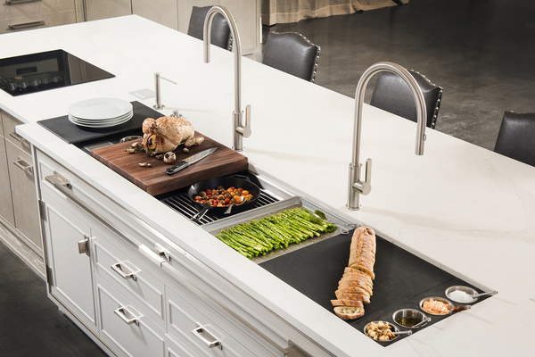 Modular workstations set over a large sink are getting people to think linearly when it comes to kitchen design. Cutting boards and racks are designed to fit on the ledge of the sink, while the cooktop is within reach of freshly prepared ingredients.