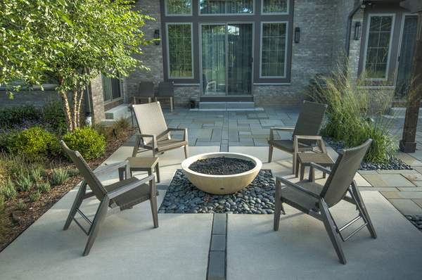 "A fire pit has its own well-defined space in this garden in Wisconsin, but careful details, including lines of bluestone intersecting the fire pit, connect the area visually to the rest of the patio. ""Details really are the most important piece,"" says the garden's designer, James Drzewiecki. ""If you're just throwing together a design and not thinking about the details, you're only filling space."""