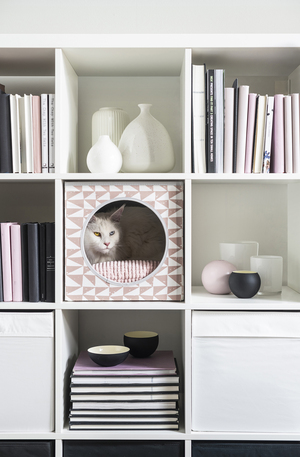 """Ikea's """"cat house"""" with pad is a cozy, safe and comfortable space that can be placed on the floor or slid into a shelving unit. A unique hidey-hole for pets, this piece ($9.99) fits into a home's decor and is easy to clean, with a machine-washable cover."""