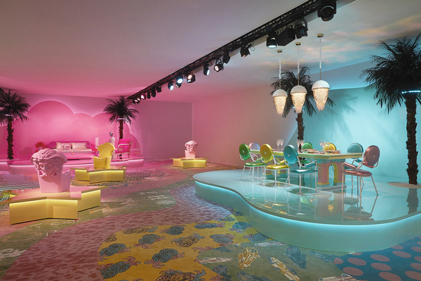 """Bikoff's design for Versace in Milan was pure magic: a set with three stages, each bathed in candy colors that changed, set on an exuberantly patterned patchwork rug that she designed, taking cues from Memphis. Versace's Via Gesu table, usually brown wood, was done in lacquered pastel colors with a colorful mirrored checkerboard top. Inspiration came from a Richard Avedon 1990 photo of supermodels wearing metallic leather miniskirts and mohair sweaters. So the chairs are clad in metallic leather. """"I wanted the pieces to feel like haute couture, straight off the runway,"""" Bikoff says."""