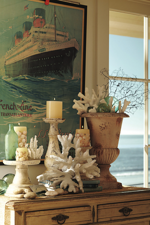 To balance out beachside decor, bring the element of fire into a space. Create small tabletop vignettes by using shells and rocks gathered beachside for inspiration. Pottery Barn also sells faux coral display pieces that start around $20.