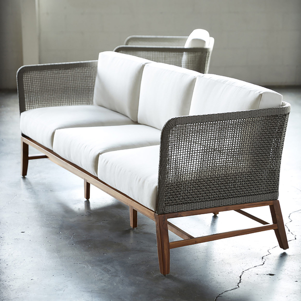 A shapely sofa from Palecek features a teak wood frame and legs in natural golden-brown finish. The double-wall back is woven with marine-grade synthetic rope in gray with maximum UV protection. The 84-inch-long by 30 3/4-inch-deep Avila sofa (and lounge chair) comes with loose seat and back cushions.