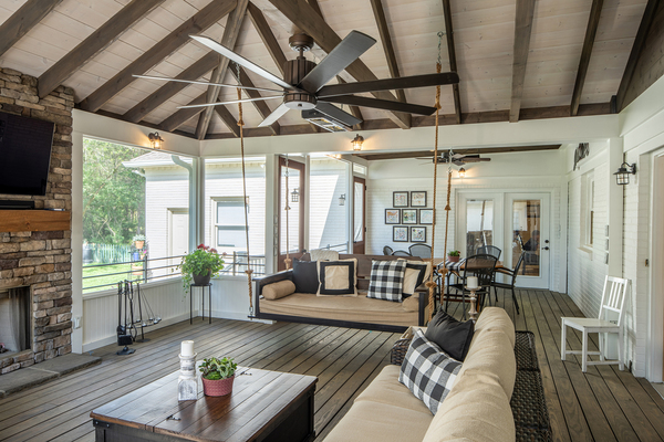 This screened back porch, designed by The Porch Co. in Nashville, provides privacy and connects people to nature and each other. Featuring a fireplace, this large back porch is a place to entertain al fresco.