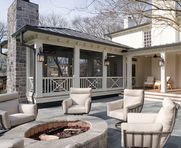 This screened porch with vaulted ceiling is an entertaining addition to the back of this home. Leading to a fire pit and patio, this structure features The Porch Company's Southern Cross panels, made of low-maintenance cellular PVC, which start at $125.