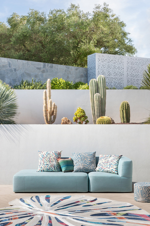 A sleek, modern, modular, padded chaise lounge and island sofas in the colors of the sky and sea are complemented by organic patterns and stripes. The inspiration for the design is the exotic philodendron leaf, part of the Magic collection for Missoni.