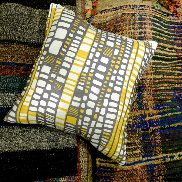 Alexandra Petrache introduced a spirited textile collection called HALFDROP at Heimtextil Messe Frankfurt. This Layers Yellow pattern was inspired by antique rag rugs in her native Romania. Traditionally made of strips of odd fabrics, woven in place with threads, the layering and collage practice were reinterpreted, translated into bold, organically layered pattern in acid tones of mustard yellow tempered by complementary grays. Hand-drawn lines make the pattern more fluid. The 20-inch pillows are made of 100 percent cotton.