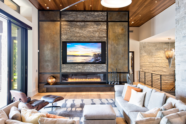 This media room, designed by The Premier Group out of Carmel, Indiana, is a retreat at a lake house, where the owners come to relax and get away. Speakers are hidden, and ambient lighting on the ceiling is plentiful.