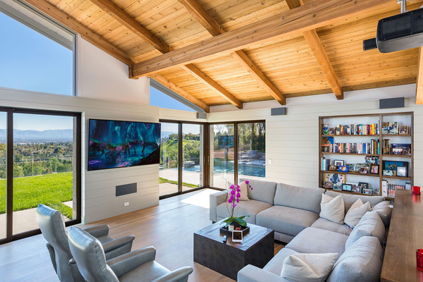 "DSI Luxury Technology of Van Nuys, California, created a media room that complements the homeowner's ""million dollar view"" without detracting from it. Motorized shades on either side of the television screen go up and down easily to cut down on glare and distractions when needed."