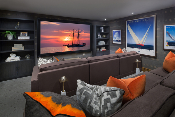 Audio Images in Tustin, California, designed this home theater/media room hybrid in a home's basement. Speakers are stashed behind fabric on the wall as the room opens up to a snack and bar area.