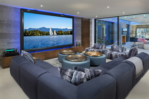 "Audio Images in Tustin, California, designed this media room for a homeowner who likes to entertain. The ""inside-out"" experience includes an entire wall that consists of movable glass panels, which opens into a large courtyard."