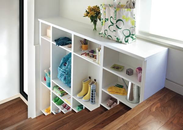 Utilizing lost storage space over a staircase keeps an entryway organized. These cubbies create a place for everything, so everything is in its place.