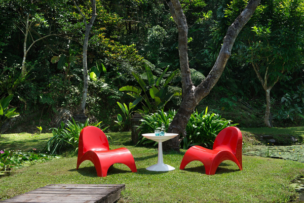 "Inspired by the flowers of the trumpet vine, which has large, pendulous, trumpet-shaped flowers, this new curvy chair from Lagoon is called ""Angel's Trumpet."" Shown in red and available in amber, white and black, the stackable chair is made of weather resistant, easy-to-clean polypropylene. The shape supports the curves of the body, and the design also prevents water retention in the seat."