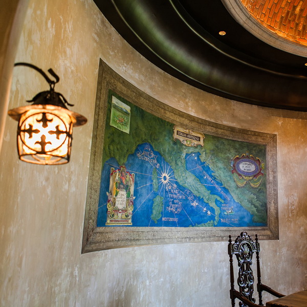A plaster piece de resistance located on the curvilinear wall in the dining room of a Tuscan-style villa features Jennifer Bertrand's hand-painted map of Italy modeled after painted images in the Gallery of Maps room in the Vatican Museum. While the sandstone-colored plaster was still wet, Bertrand added green and blue pigments to color-block the land and sea.