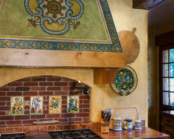 A new range hood has old world appeal in a Mediterranean tile motif with a painted patina, created by Jennifer Bertrand.