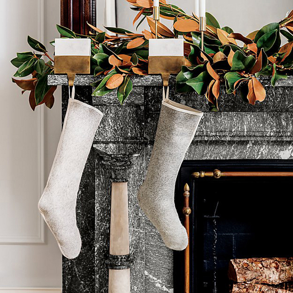 Kara Mann makes stocking holders tres chic at CB2. White marble sits squarely in an antique brass finished base with a single wide hook. Nestled in a magnolia garland, visually warmed by its copper-hued underside, along with brass-plated steel candleholders, the vignette is perfection.