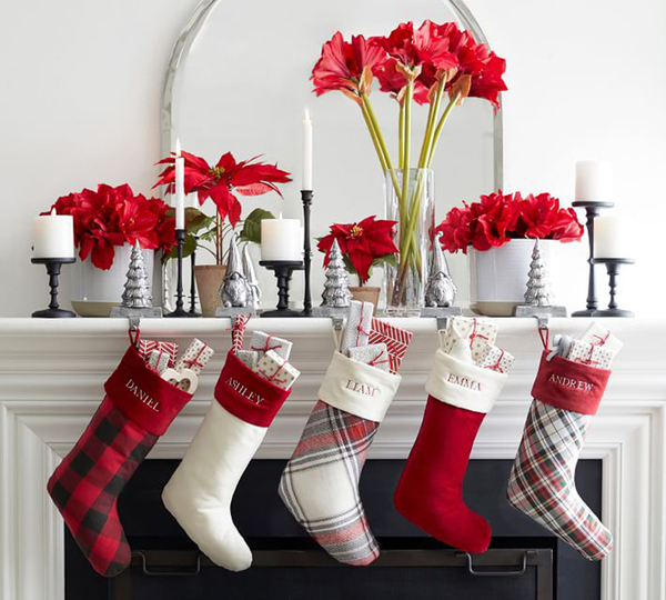 Pops of red lend vibrancy to this living room. Personalized stockings combine a red-and-white motif in solids and plaids. The Buffalo check is 100% cotton; Denver plaid, cotton/linen blend; Hamilton plaid, 100% acrylic. A collection of faux red blooms include poinsettia and amaryllis, all available at Pottery Barn.