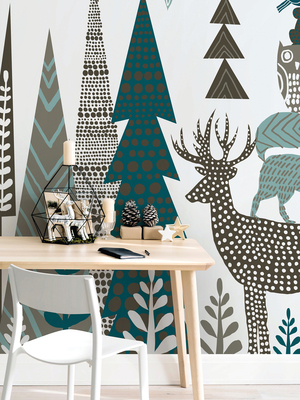 An enchanting fantastical forest in a folk art interpretation includes stylized trees, fronds and reindeer fancifully decorated with polka dots in a palette of teal, black and white. The peel-and-stick wallcovering is from Wallsauce.