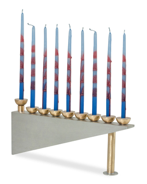 This contemporary architectural menorah, by Joy Stember Metal Arts Studio, gets a dash of sass from skinny striped tapers. The nine-branched Modern Geometric candelabrum is lit during the eight-day holiday of Hanukkah. The ninth candle, the shamash, or helper, is used to light the other candles. The piece measures 10 inches wide by 5 inches tall and is made of pewter and brass.