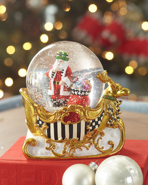 The charm of snow globes knows no age barriers. This one, from MacKenzie-Childs, available at Neiman Marcus, features Santa and gifts, with the snowy globe perched on a resin gold sleigh, the side panels are decorated with the brand's signature black-and-white stripes and checks.