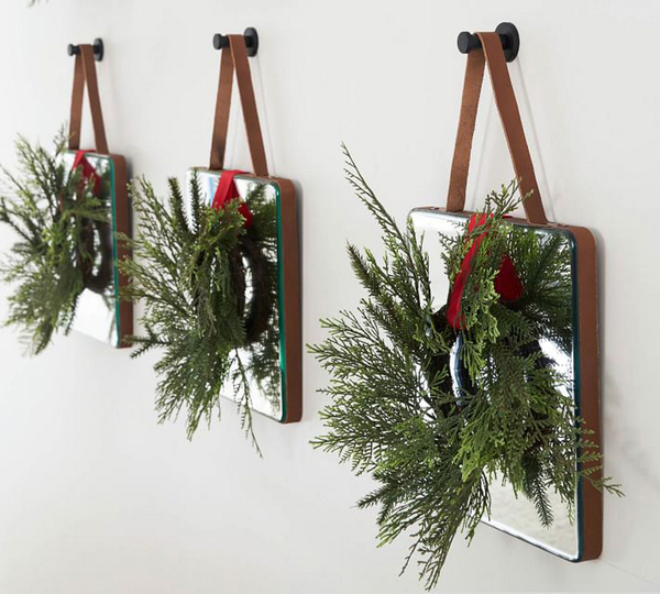 Grouping objects makes more powerful displays. Pottery Barn shows off stylish new square leather-wrapped mirrors, with matching saddle leather hangers. Faux pine wreaths with red ties make them festive for the holidays.