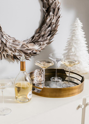 Simplicity is power. Kara Mann sets out some of her glasses for CB2 on a burnished gold-mirrored gallery tray, teams it with a gold-topped decanter and adds a holiday flourish with a feathered wreath and small white feather tree.