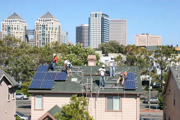 In 2020, every new construction project of single family homes in California will be required to have solar units built onto roofs. Here, in Oakland, California, workers install solar panels onto a rail system.