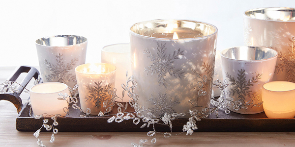 Gather votives of different sizes in a small tray, to be set on a cocktail table for a beautiful glow. These mouth-blown glass candles are crafted from glass and glitter, with snowflakes etched in. Available in large and small sizes, with scented candles that include notes of cypress, roasted chestnut, vanilla, fig leaf, sandalwood, papaya flower, benzoin and patchouli. All, plus the metal tray of aluminum with antique gold finish, are from Pottery Barn.