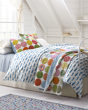 Charming mini prints recreated from original hand-painted art work epitomize summer themes in percale sheets from Garnet Hill. Shown here on the duvet are whales in lapis. Other themes include Adirondack chairs in aqua; shells in coral; buoys in Oxford; sand dollars and sea turtles. On the hand-quilted Johanna quilt, sham and pillow cover: cheery circular patches of retro prints modernized by bright colors.