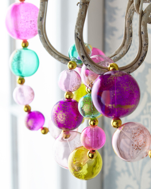 Vivid ornaments in magenta, turquoise, lavender and yellow strung with gold beads add a festive air to the arms of a chandelier. The One Hundred 80 Degrees Ball Garland is from Horchow.