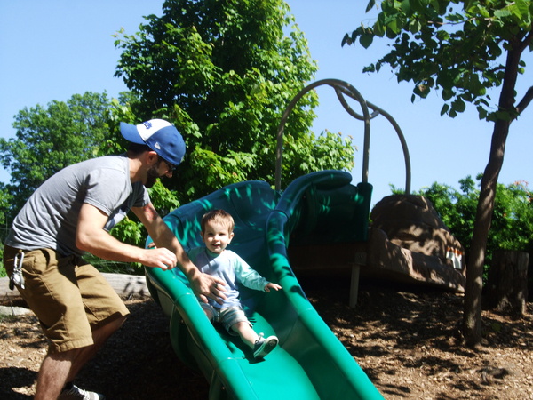 This 2-year-old is experiencing his first time down the slide. Dad is there, and he's having fun, too. Let public parks inspire your own play space in the backyard, and make it a place that's inviting for kids and adults.