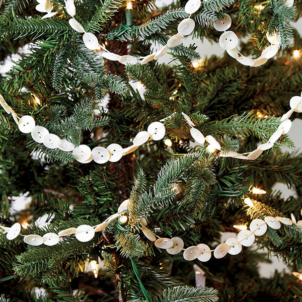 Wafer-thin white buttons are strung in a simple garland on a fir tree. The Marianna Button Garland from Ballard Designs is crafted from iridescent capiz shells, which change color in light, casting a pearly glow. Each section is nine feet in length and is sold in a three-section set.