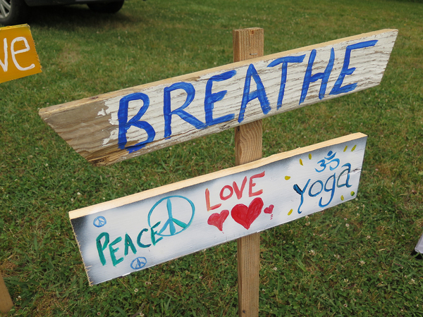 At a weekend yoga retreat, signs reminded visitors to breathe deeply and experience the spirit and energy of yoga outdoors.