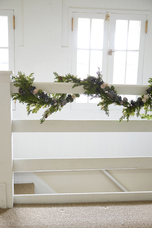 A second-floor railing is a great spot for a little holiday cheer. This realistic faux juniper bough with pine cones if from Terrain.