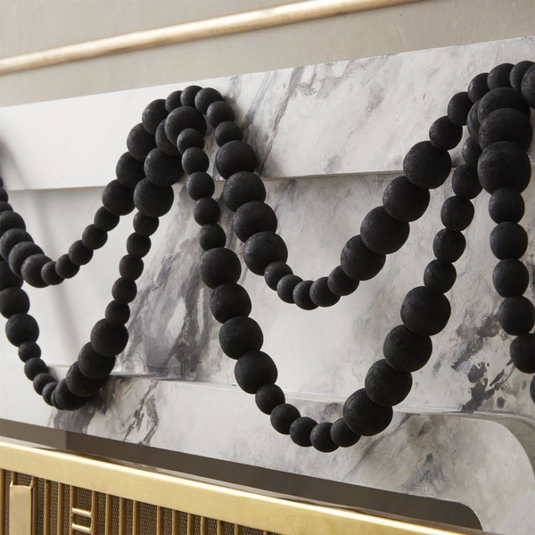 Garlands crafted from matte black wooden beads, exclusive to CB2, are fashionably graphic with a minimalist attitude on a white marble fireplace mantel.