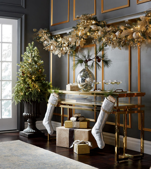 A thick garland from Frontgate is made up of faux greens, ornaments, crystals, gold metallic ribbons and gold-edged forest green ribbons that lend opulence. The Gilded Elegance garland lavishly draws the eye above a brass console in a room punctuated with gold picture moldings.