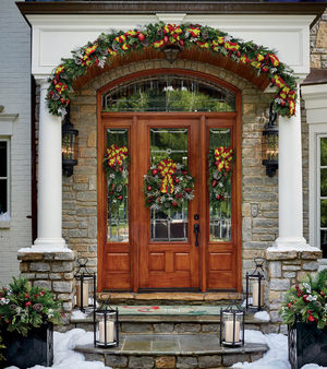 A White Christmas Frosted garland from Frontgate has a lively look, with its zesty lime-on-red patterned ribbon, red ornaments and white snowy pine cones and leaves. Curved to the arch above the front entry of a home, the garland coordinates with a cordless wreath and swag decorations. Boxes filled with greenery and lanterns add to the welcome.