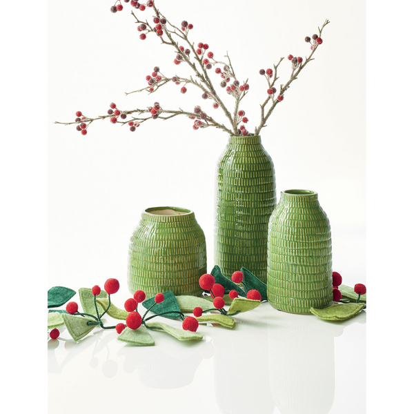 "Simple felt triangle ""needles"" in two shades of green with clusters of red pompom berries form a handcrafted garland that is part of an attractive tablescape, with textured glazed embossed dash stoneware vases, one holding a berry branch. All are from Crate and Barrel."
