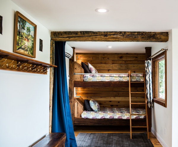 Salvaged barn beams and paneling were used to create a custom-made sleeping sanctuary in a nook of this 1973 A-frame house, located near the Blue Ridge Mountains in Virginia.