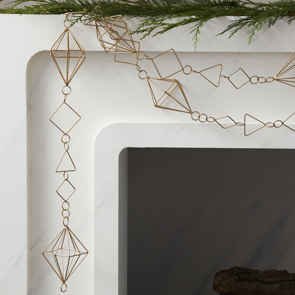 A series of geometric shapes in different sizes create a fancy chain that looks like a necklace -- simple and modern on a white marble mantel. The garland is from CB2. Credit CB2