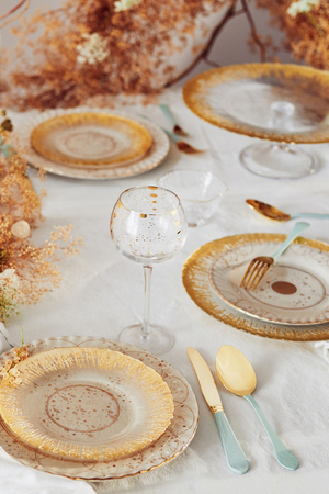 A combination of gold-rimmed soda-lime glass with more rustic stoneware plates elegantly dress this table. The gold of the bordered Thistlewhit pieces beautifully blend with the russet tones in the decor. A surprise touch: gold Renscenca flatware with cool seafoam handles, all from Anthropologie.