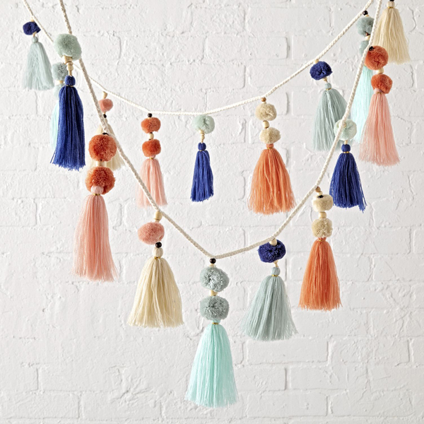 "Playful tassels and pompoms in peachy pastels, teamed with pale to deep blue are ""like a party for your decor,"" says Crate and Barrel."