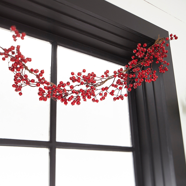 A red berry garland from Wisteria is a stunning foil to a black window frame.