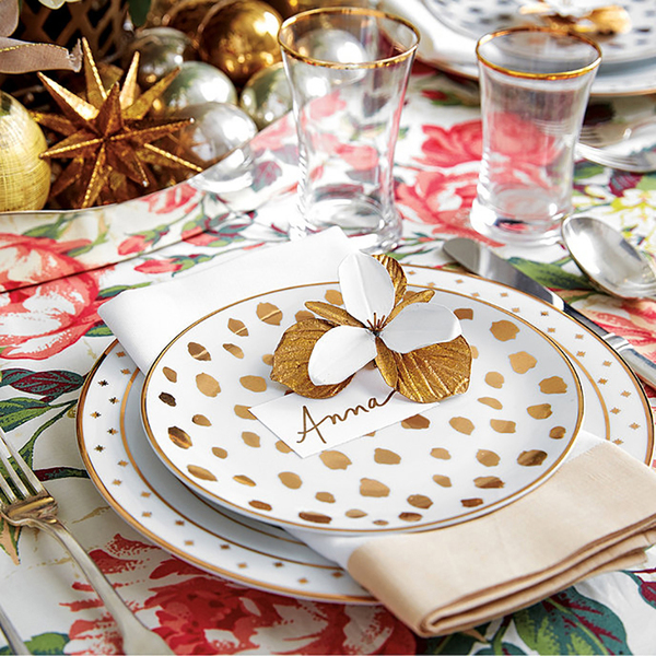 A fashionable cheetah print goes glam in gold, in accent plates topping Bunny Williams' Gold Star bordered plates from Ballard Designs, which pop on a bold floral-patterned cloth. The centerpiece is a silver metal container stacked with gold and silver ornaments.
